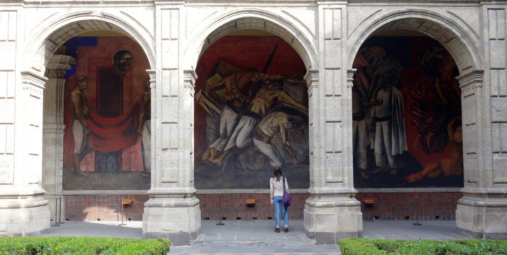 Dr. Lauren Kilroy-Ewbank in front of José Clemente Orozco's The Trench (center arch), San Ildefonso College courtyard, begun 1923, Mexico City